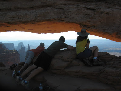 three kids leaning into Mesa Arch