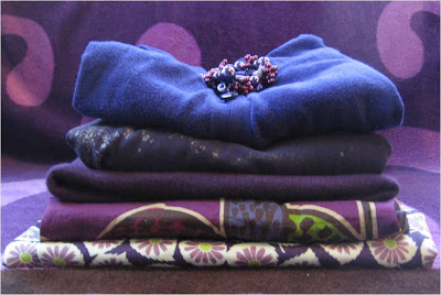 stack of purple sweaters and fabric