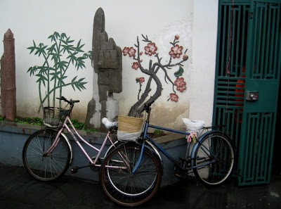 two bikes leaning against a white wall painted with plants