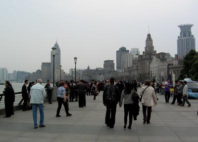 People walking boardwalk of Bund in Shanghai on a grey day