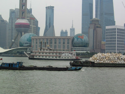 Pudong skyline behind river with trash boat