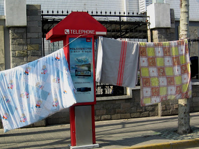 bed sheets hung on phone box in Shanghai