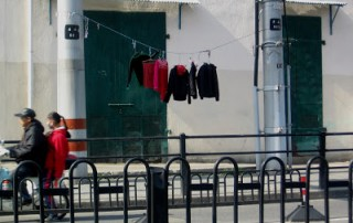 red and black laundry hung out to dry on street in Shanghai