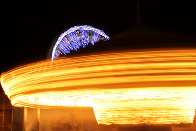 Yellow carousel lights in motion with purple ferris wheel circle behind them