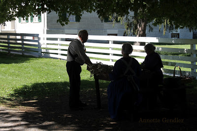 three historical actors weaving baskets outside in the shade at Shaker Village