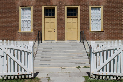 Symmetrical yellow entrance doors at family dwelling building in Shaker Village