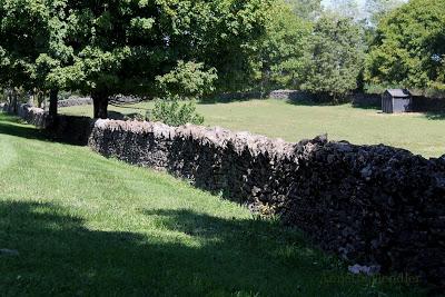 stone fence across green lawn