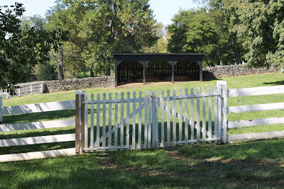 white pasture fence with stone fence behind it