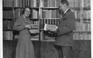 young woman with her father in front of bookshelves