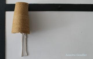 Shaker straw bonnet handing on a dark peg on white wall