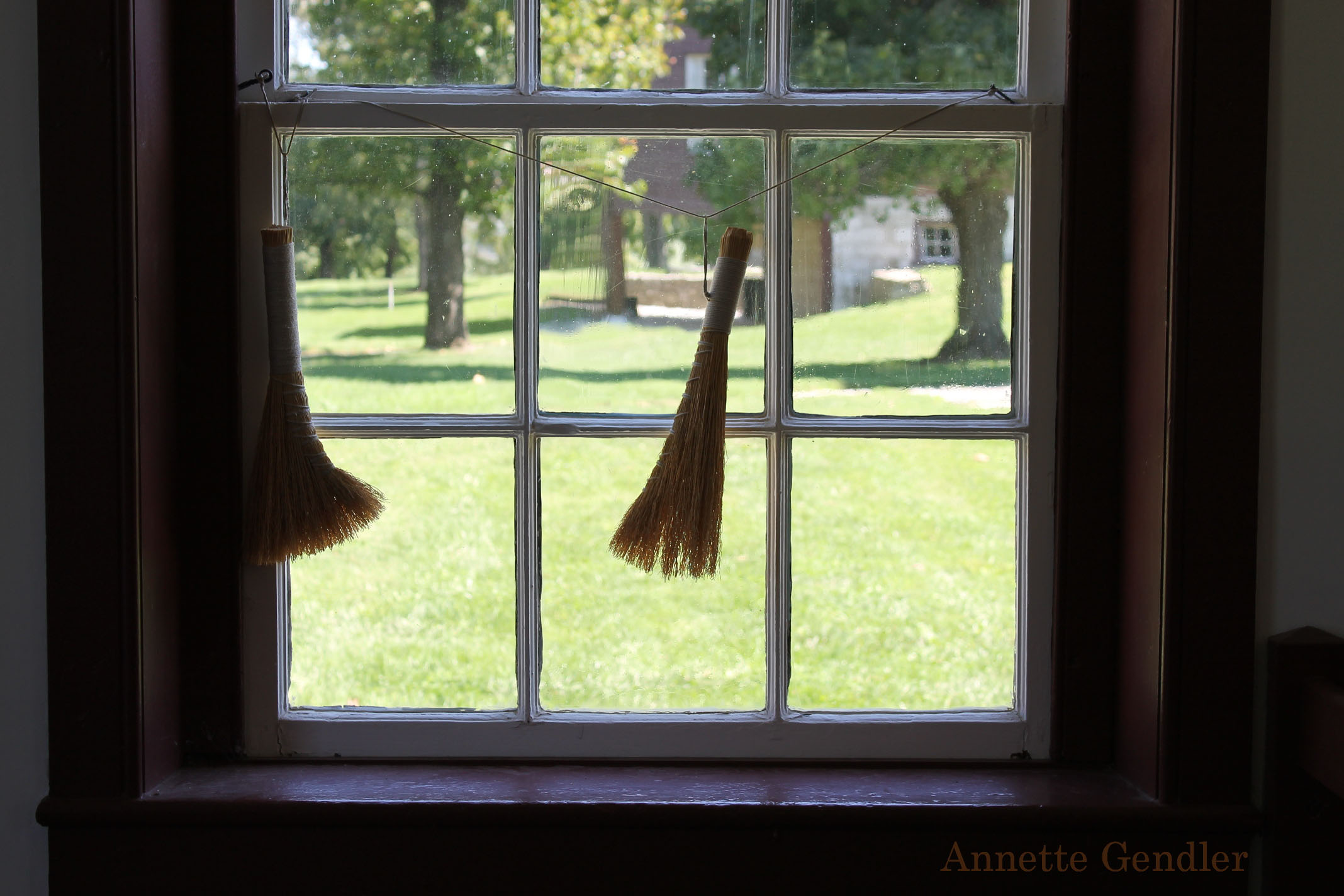 two little brooms hanging in a window at Shaker Village