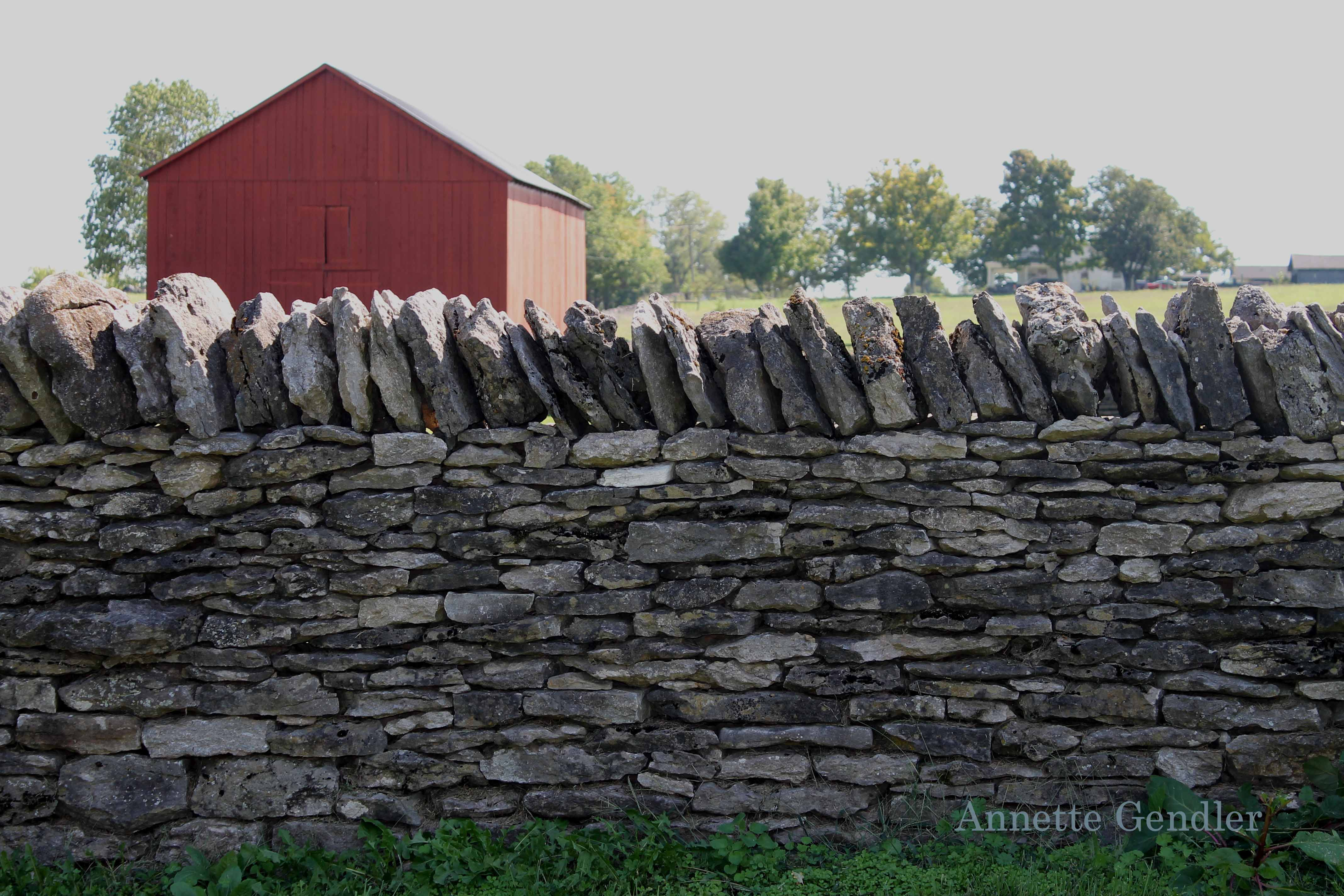 stone fence with red barn