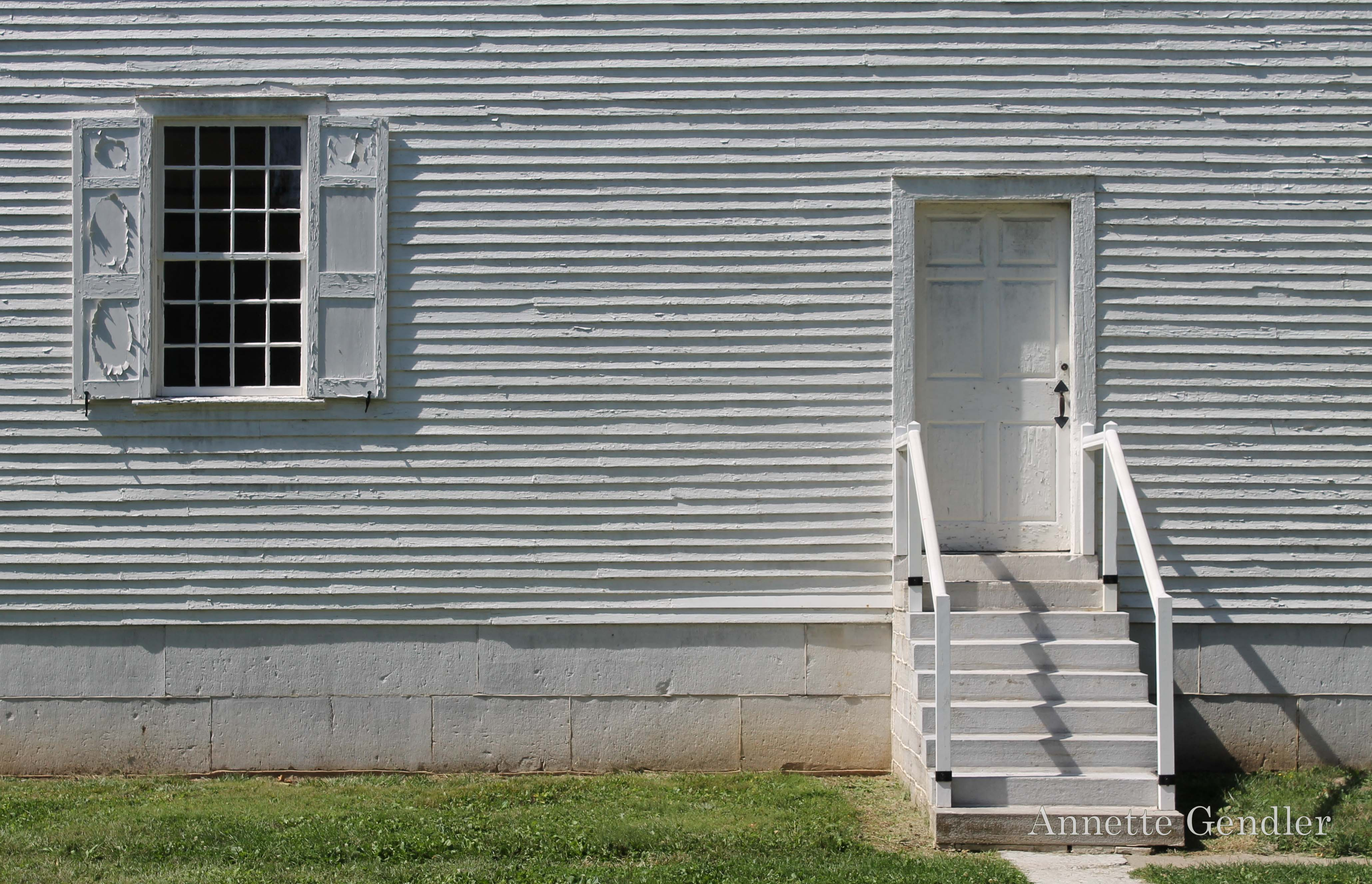 Weathered white clapboard house wall, window and door with steps
