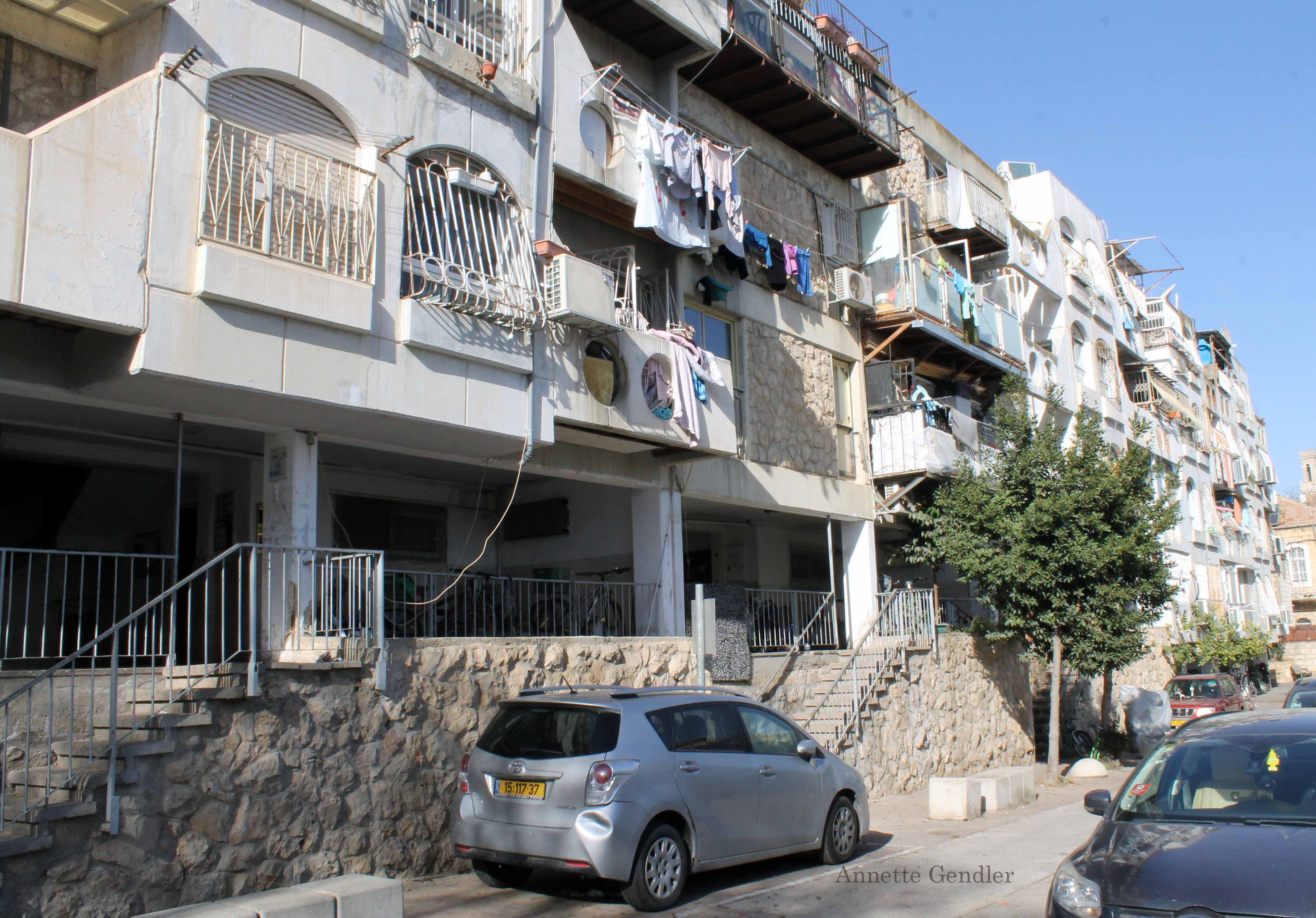 View of 1970s apartment building in Musrara, lots of balconies with laundry hanging outside