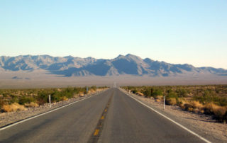 Empty, straight paved road in Nevada leading to the mountains in the distance