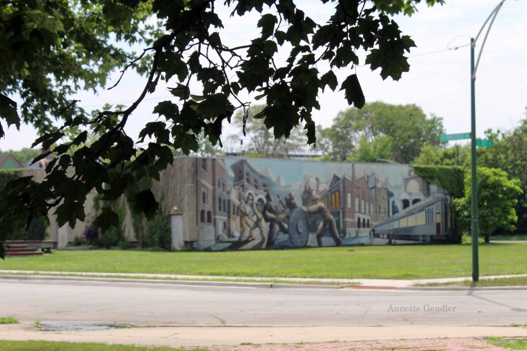 mural on current one-story temporary visitor center building depicting Pullman factory workers rolling a wheel with a railway car on the side,