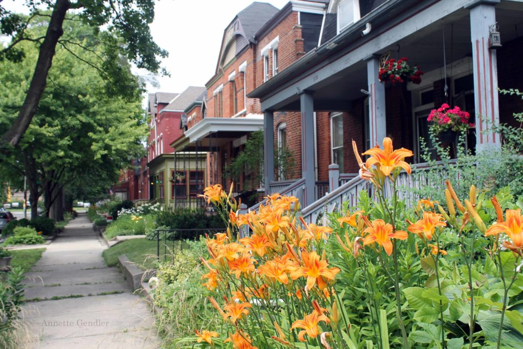 row of red brick two-stories homes with lush front yards in Pullman Historic District, Chicago, tiger lilies in the foreground