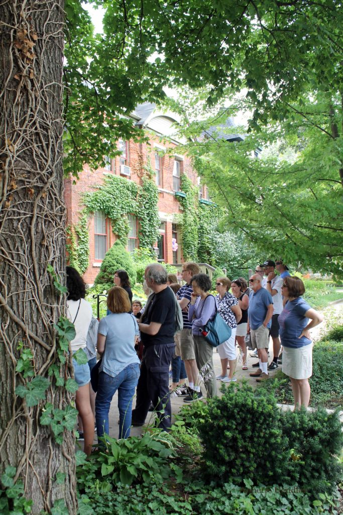 people participating in a walking tour of Pullman Historic District standing on a side walk, looking at row houses and surrounded by lush greenery