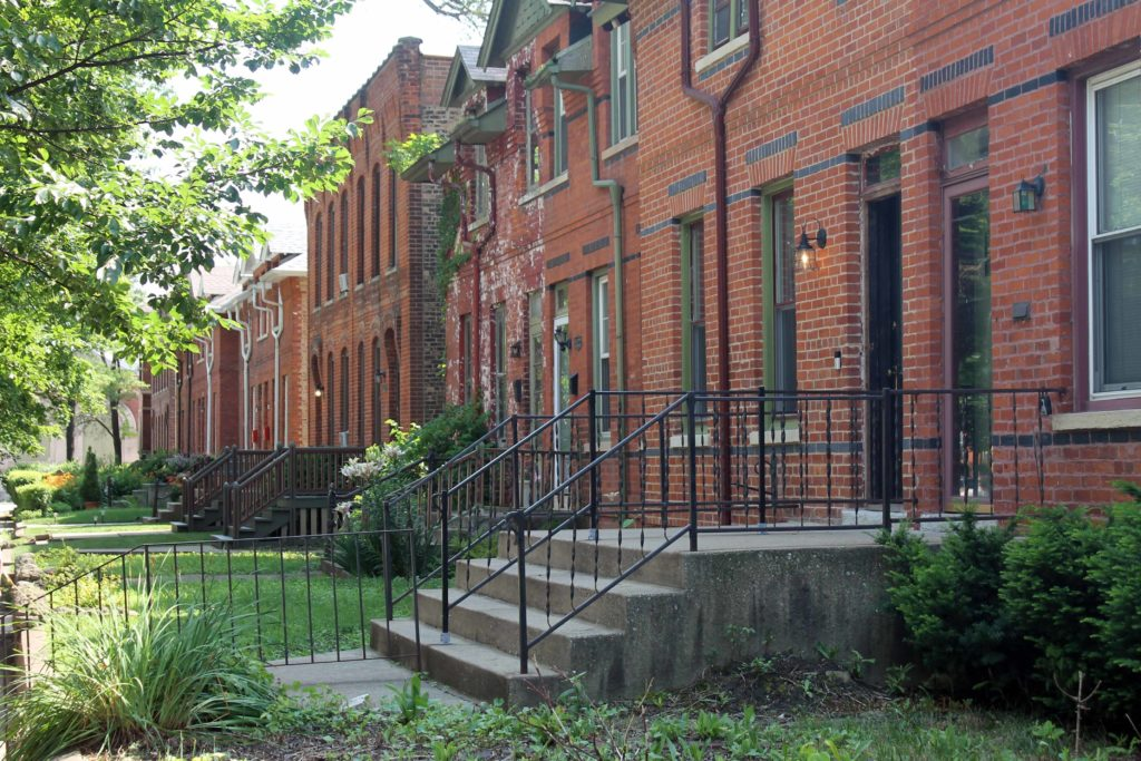 view of multiple front yards and red brick rowhouses