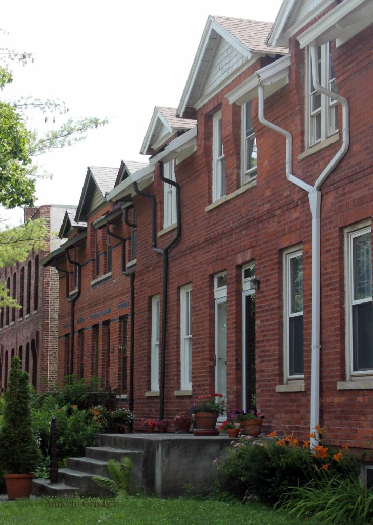 red brick rownhouses with rainpipes meandering down the sides