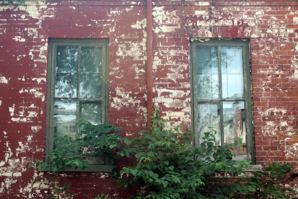 paint peeling off a red facade