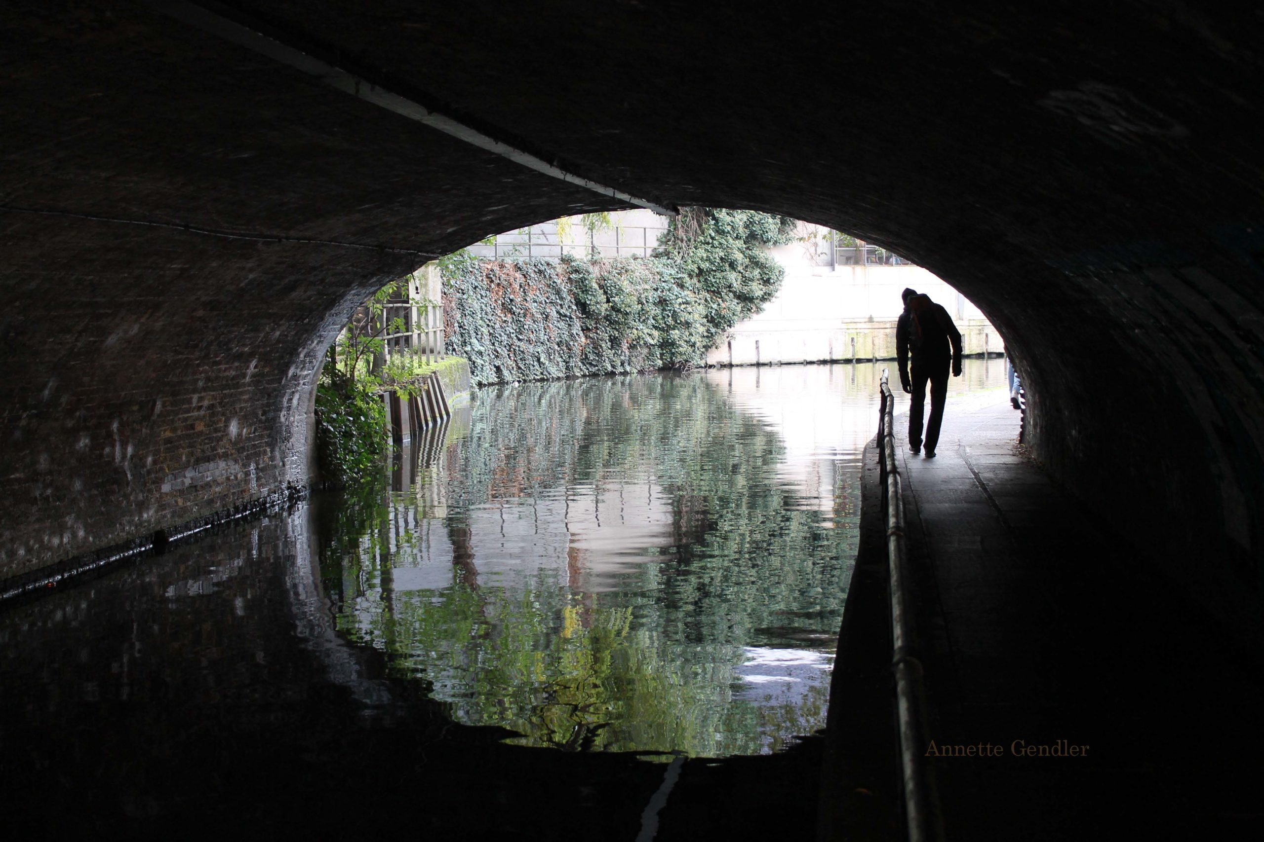 oval canal tunnel opening with black figure bending to walk through it