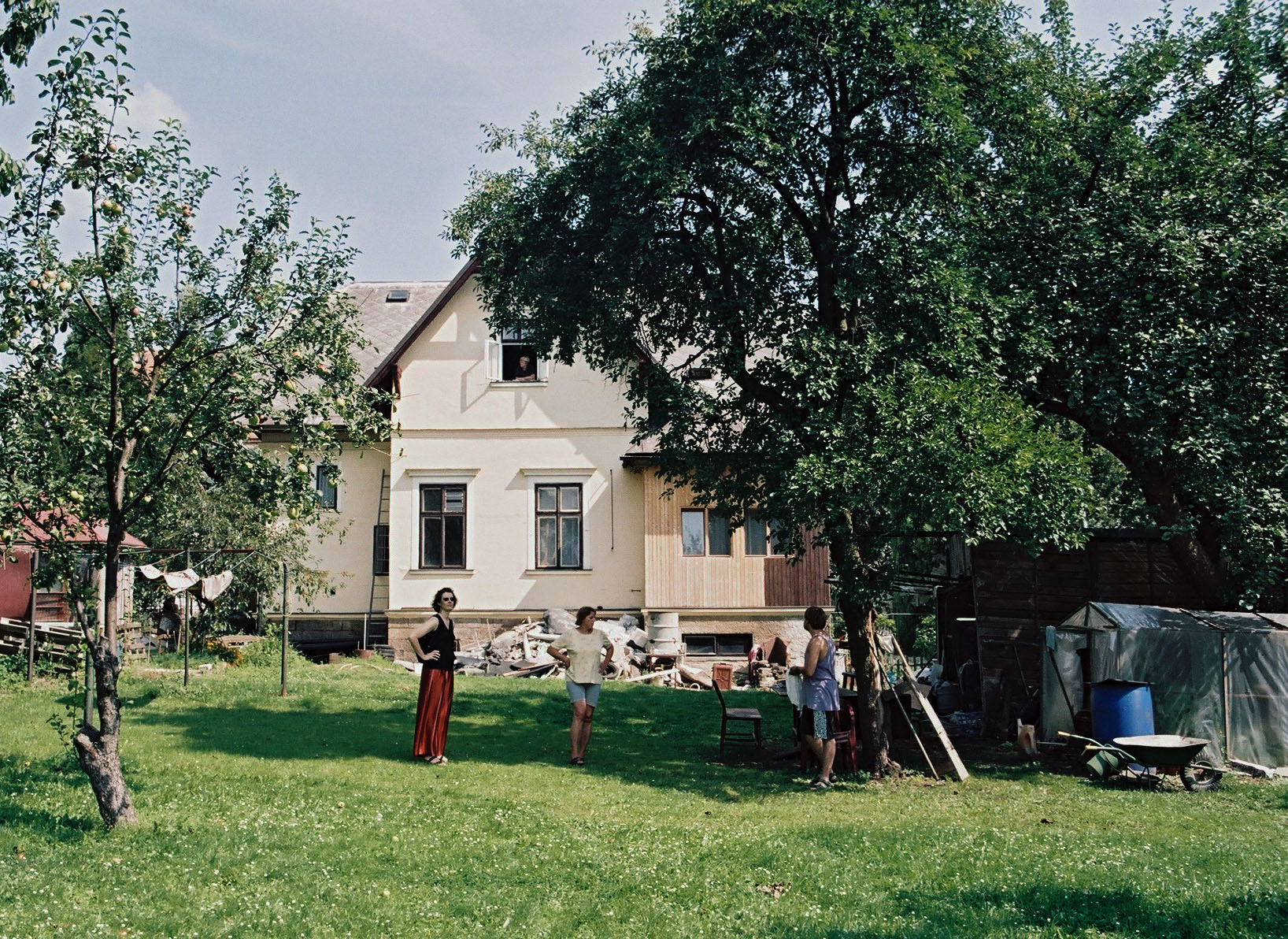 grassy backyard with fruit trees and white house in the background with three people standing in the yard