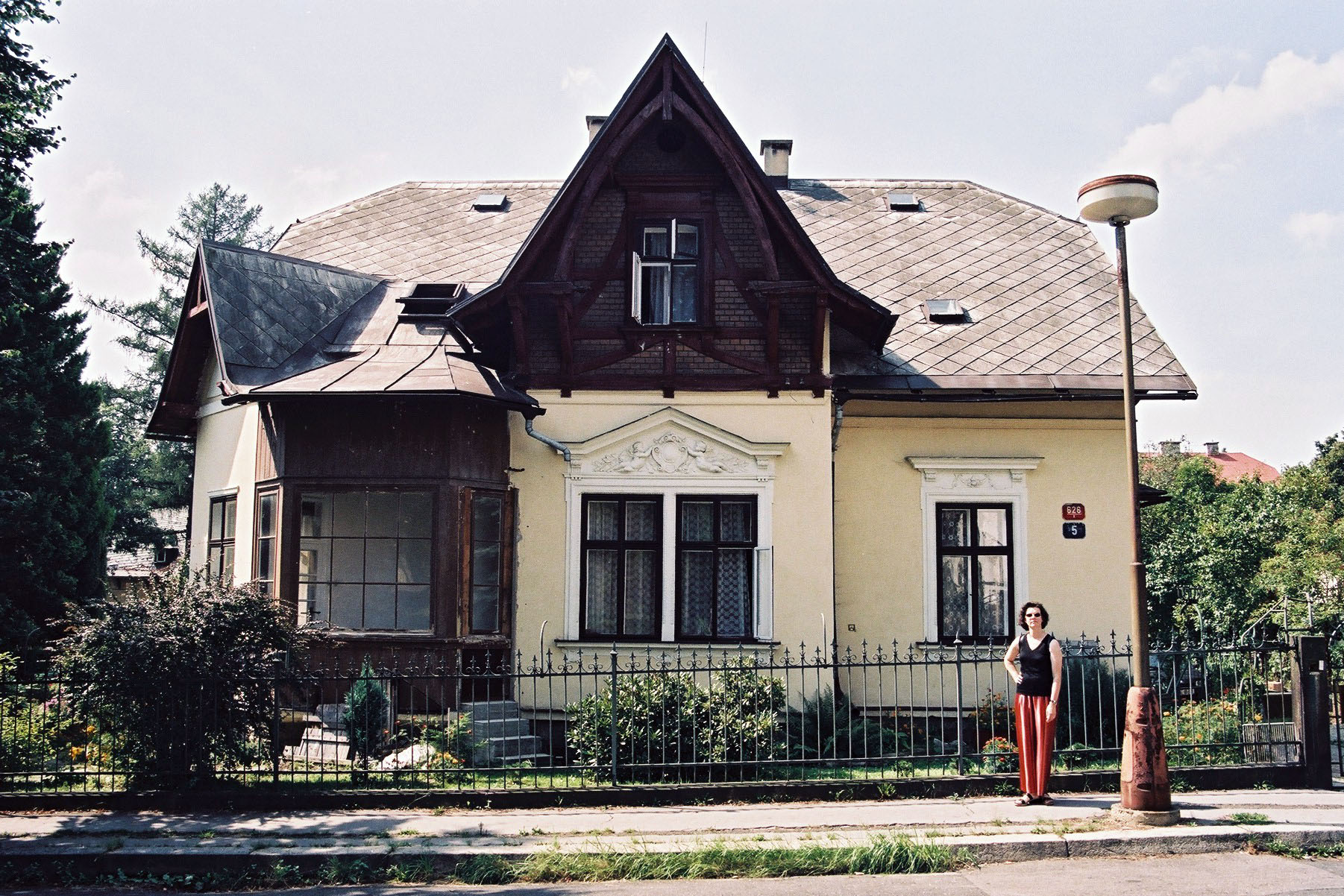 Author standing in front of her grandparents' former gabled villa in Liberec in 2002