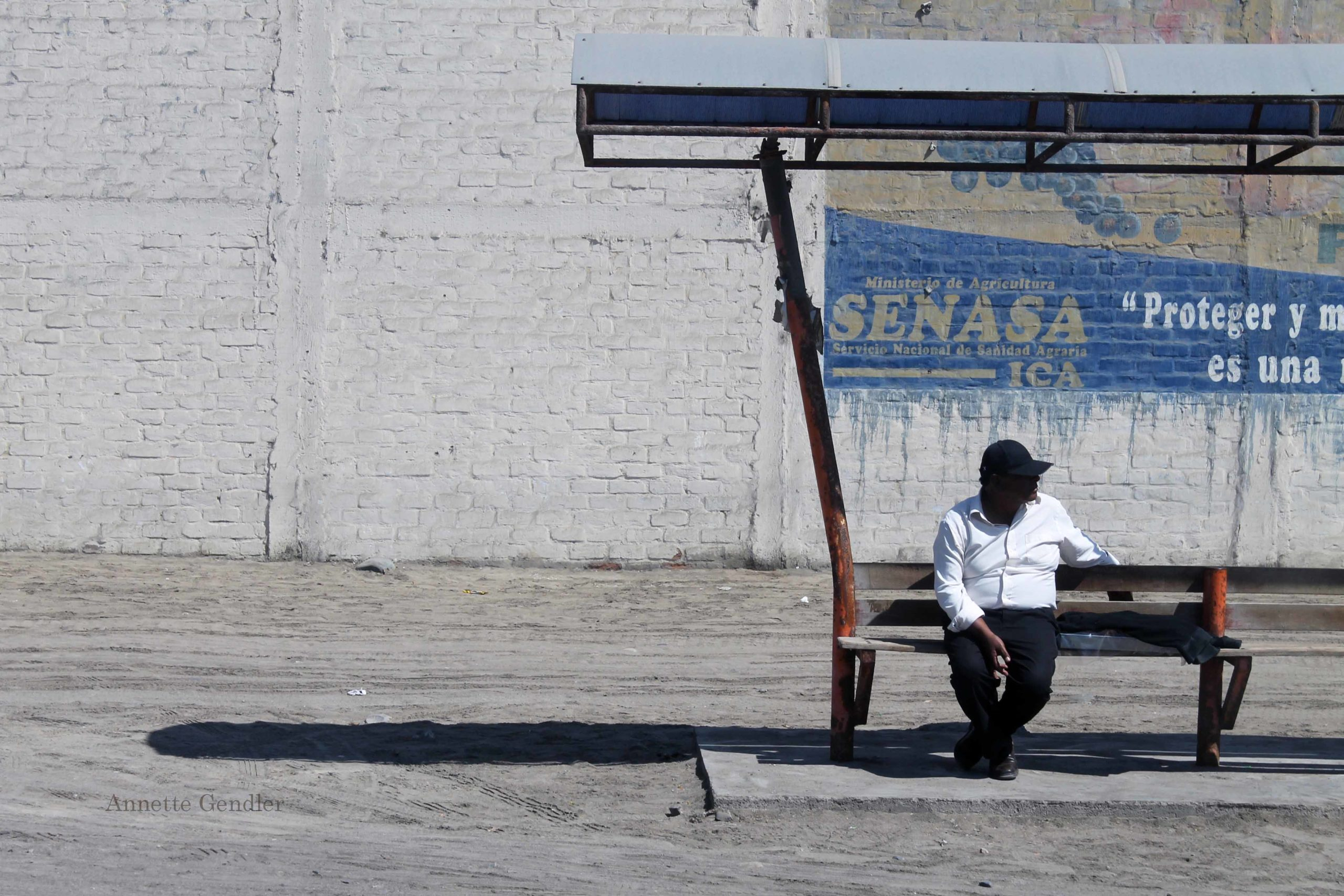 guy in blazing white shirt sitting on a bus stop on coast of Peru