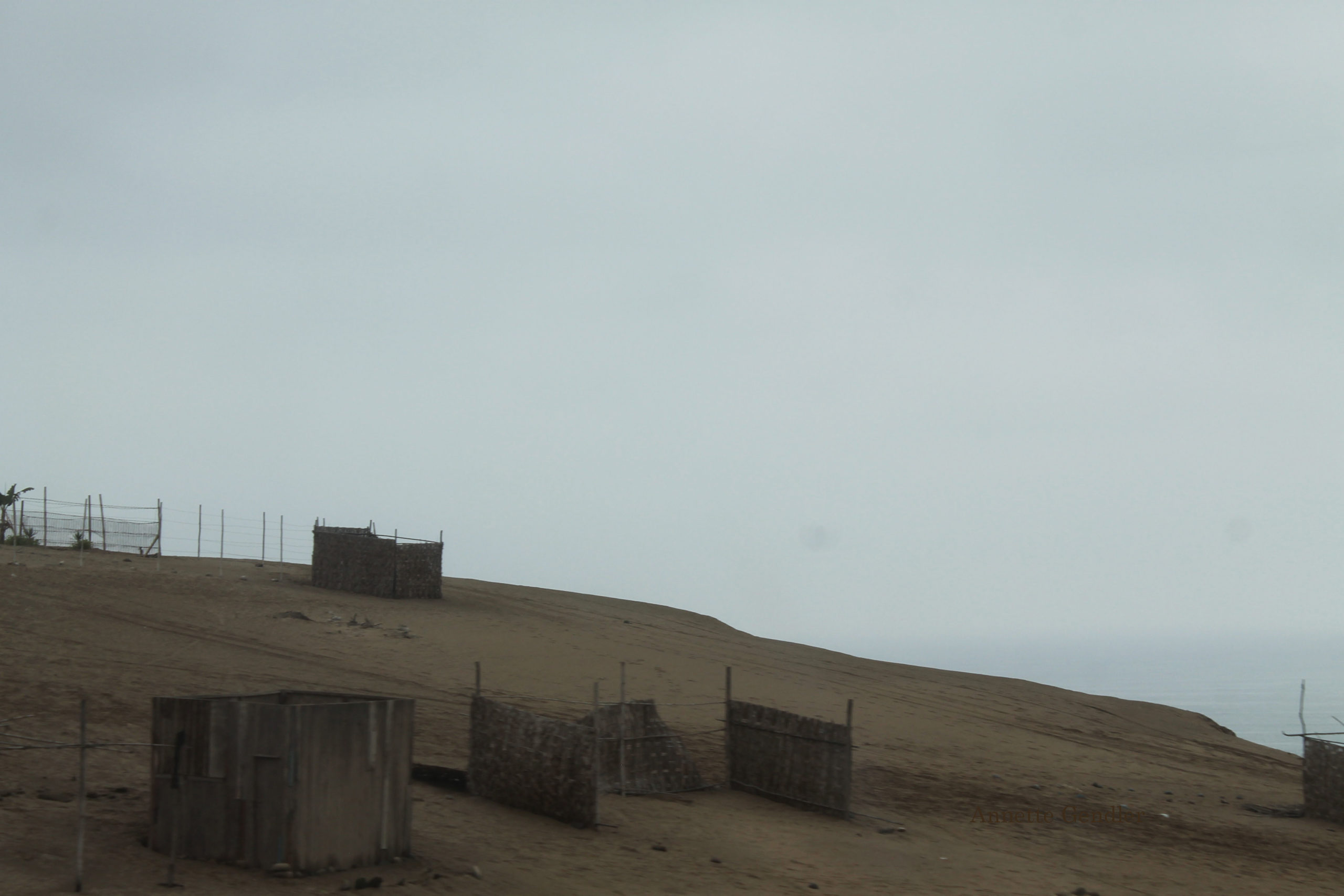 Ruins of shanty town reed huts on a sand dune on the coast of Peru