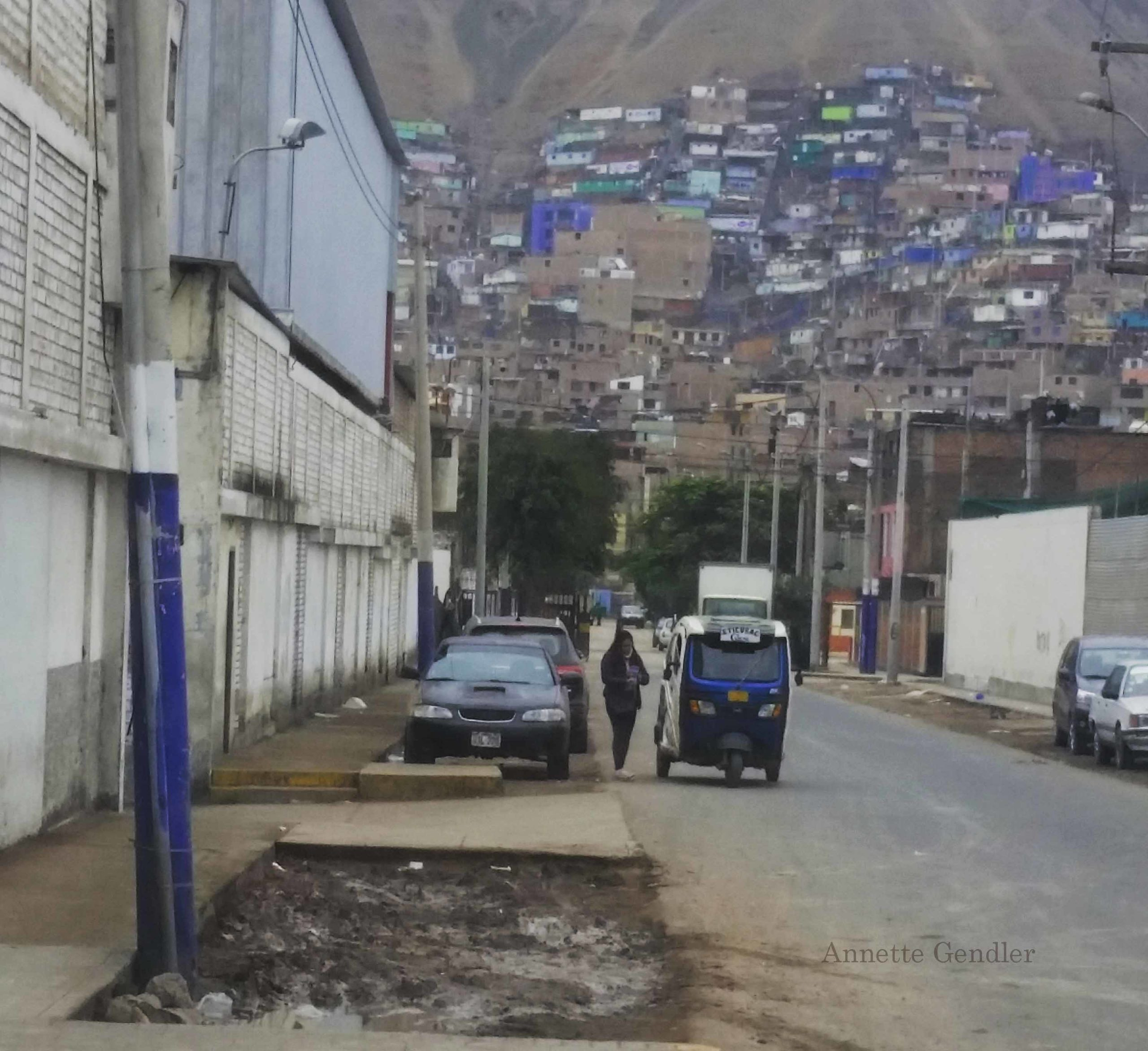 taktak car parked on dirt road in shanty town south of Peru, dirt hill with huts in the background