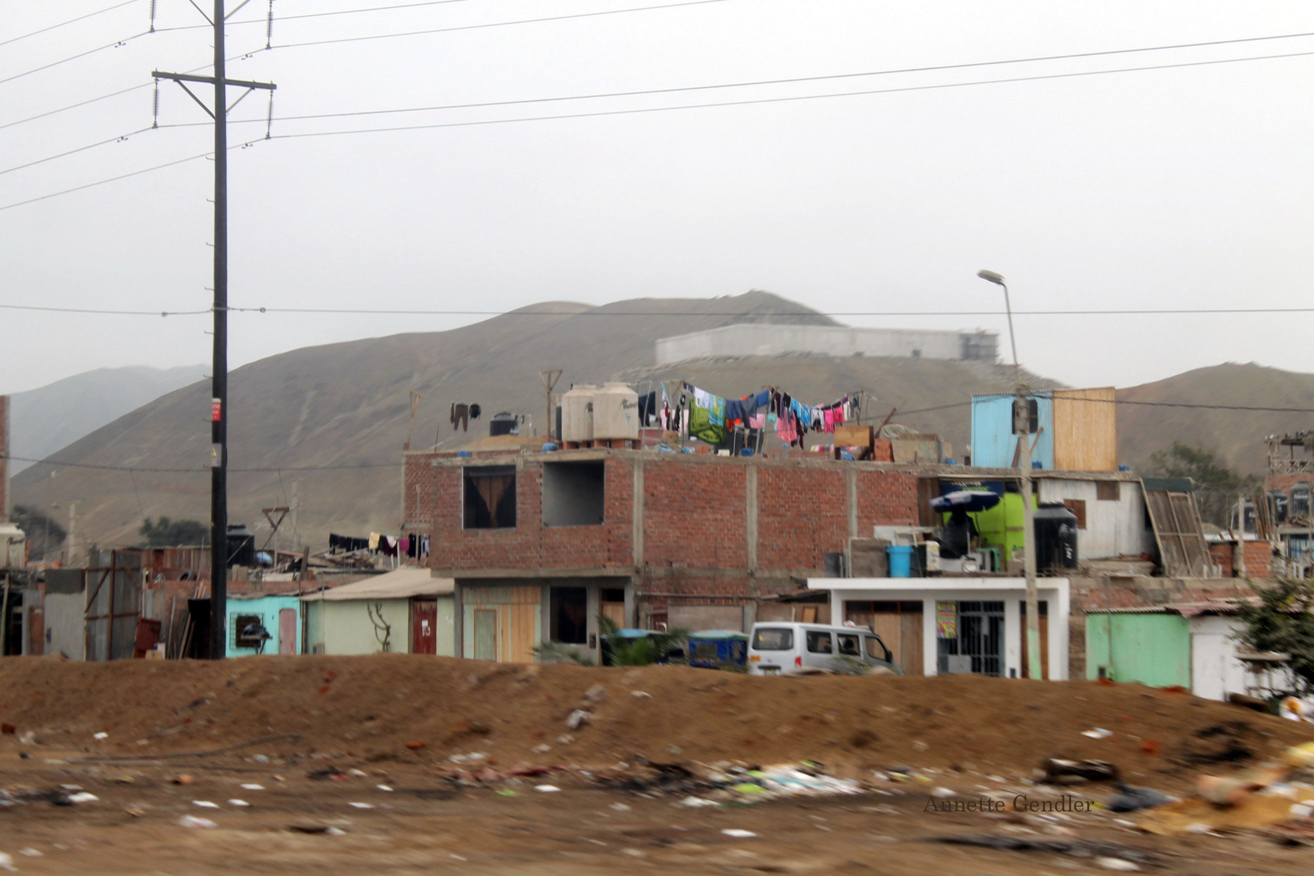 Cinder block construction in shanty town with laundry lines and water containers on roofs