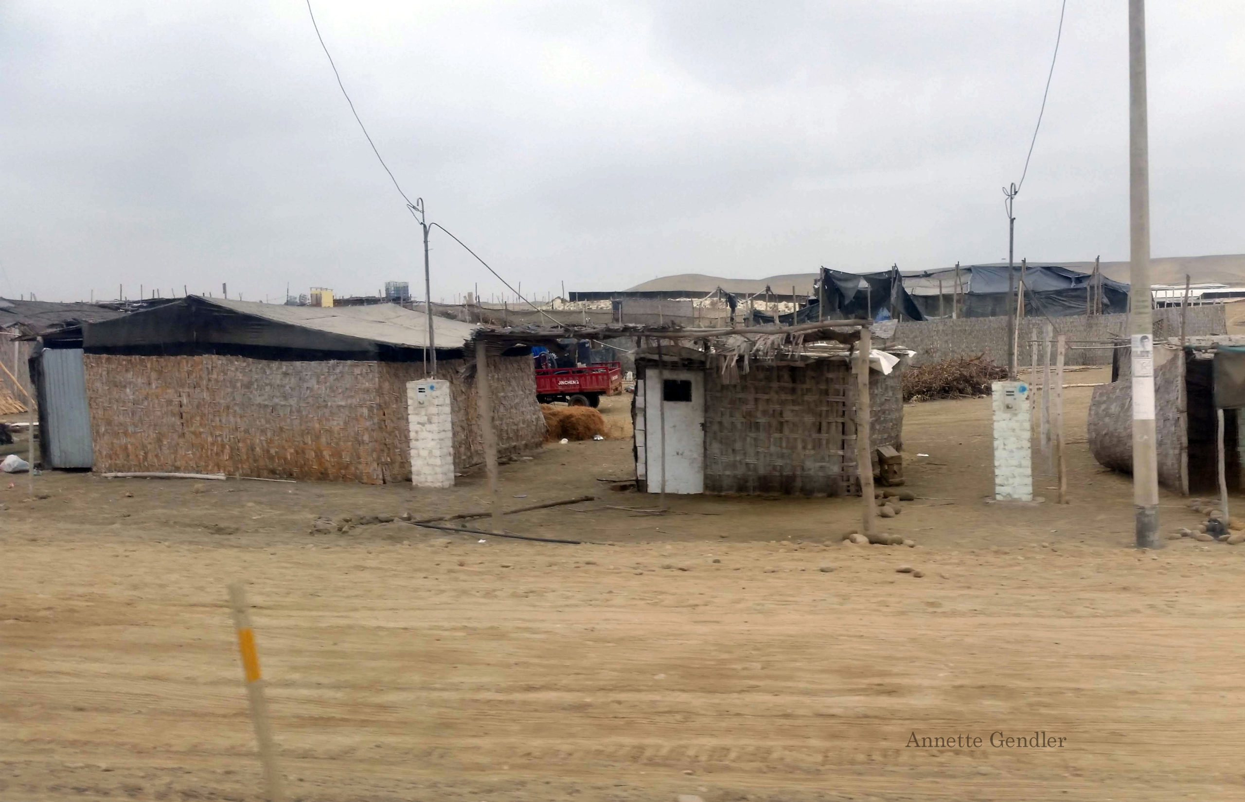 Electricity lines running to reed huts in shanty town in Peru