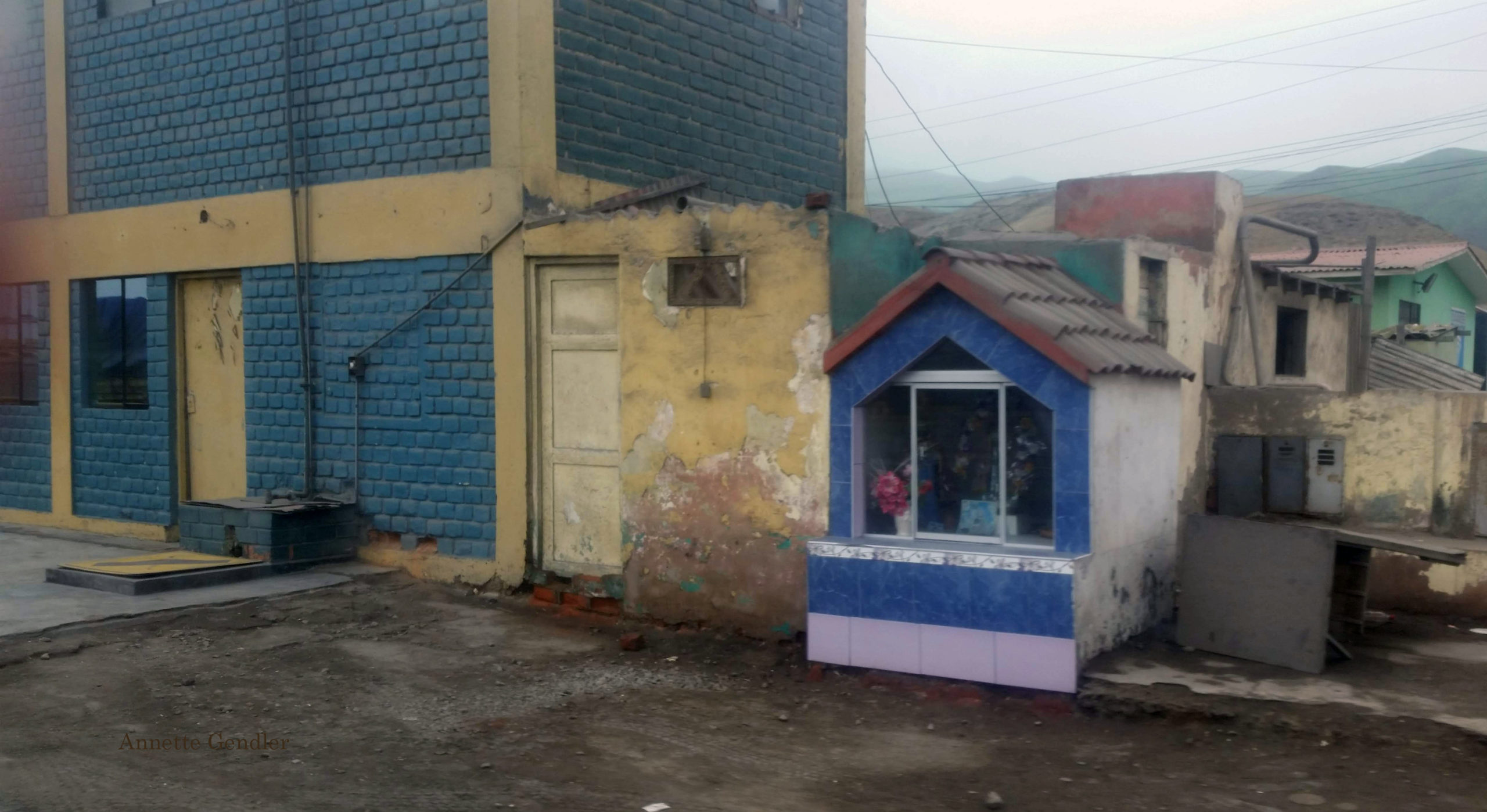 Colorful little blue stone hut shrine in shanty town