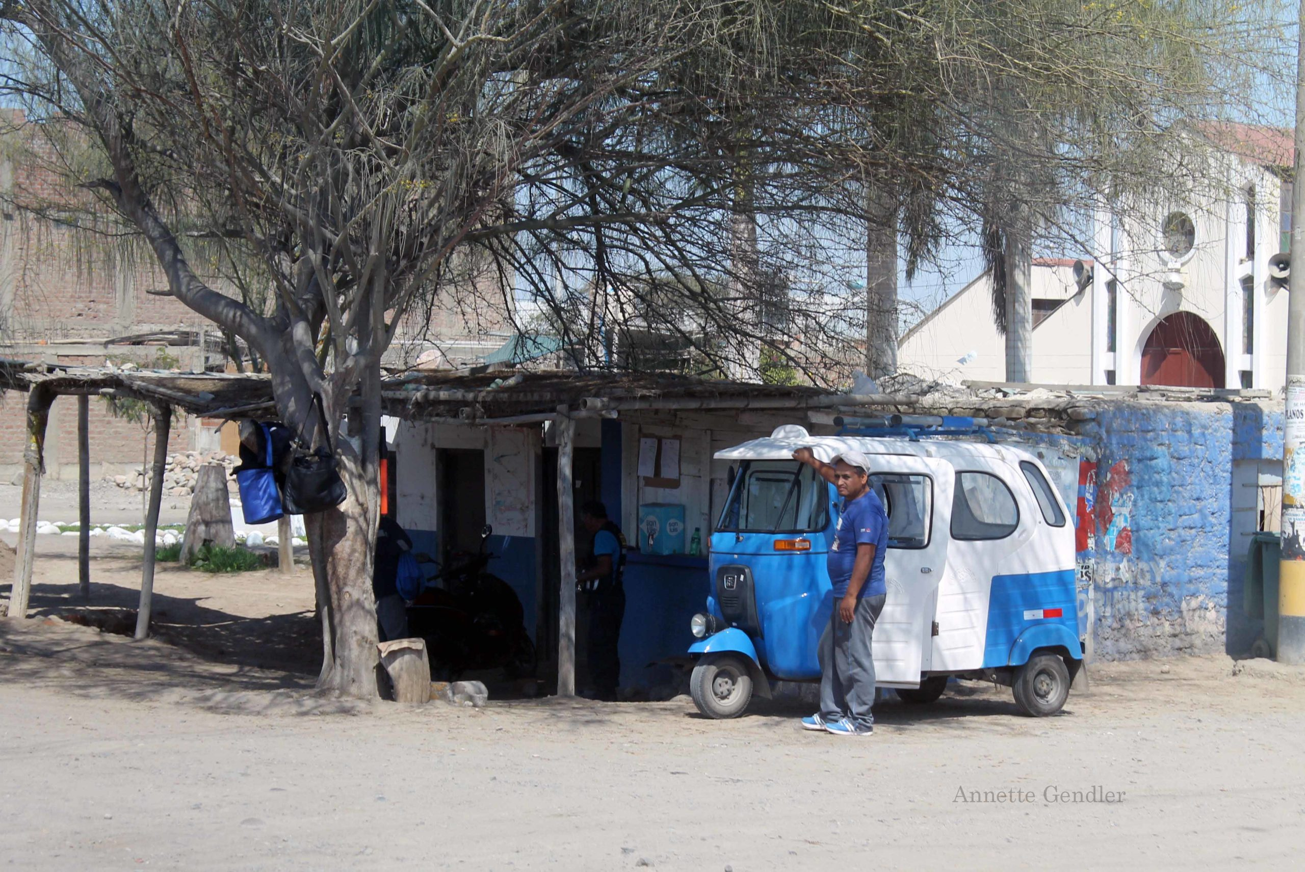cinder block hut in shanty town painted a happy blue with white and blue tactac car and its driver standing in front
