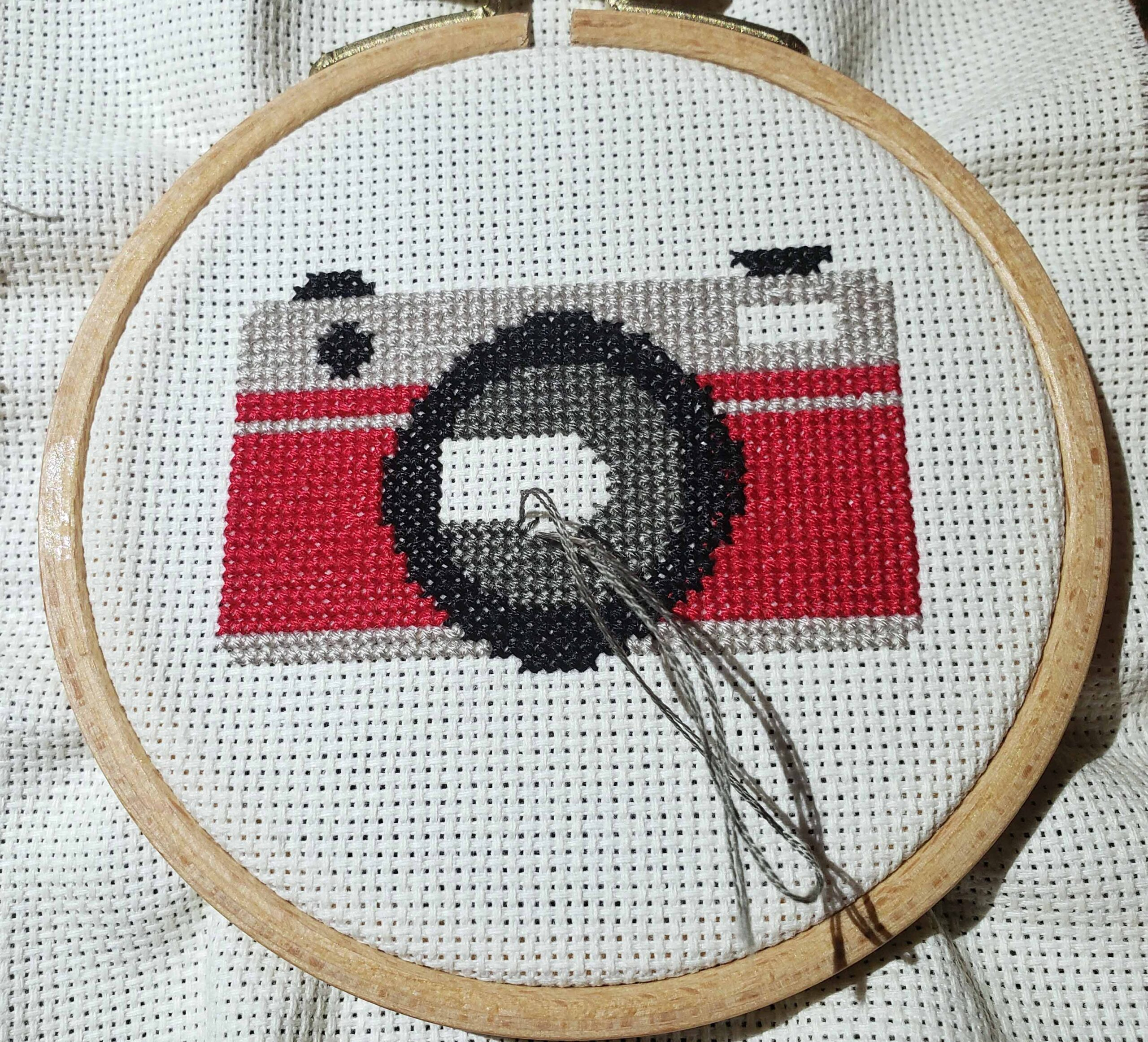 small circual cross stitch pattern featuring a camera in red, gray and black