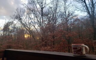 Balcony railing with bare woods and sunset